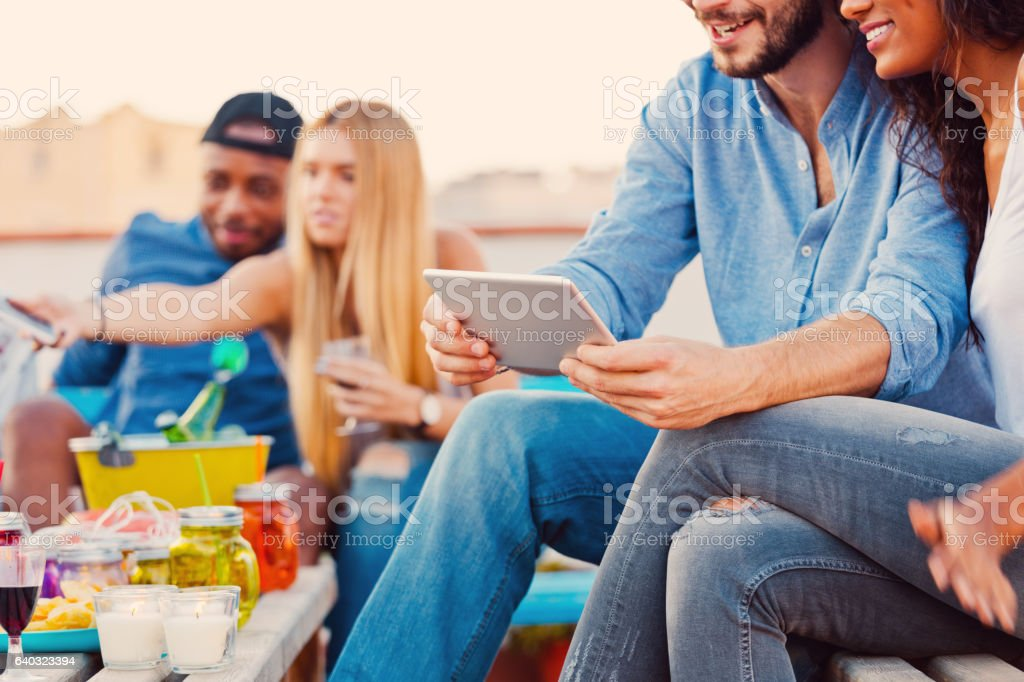 Young couple using a digital tablet at the rooftop stock photo