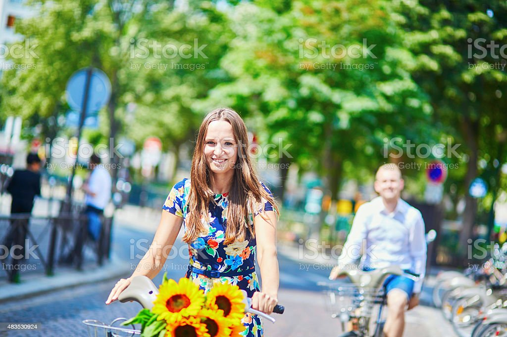 Young couple using bicycles in Paris, France stock photo