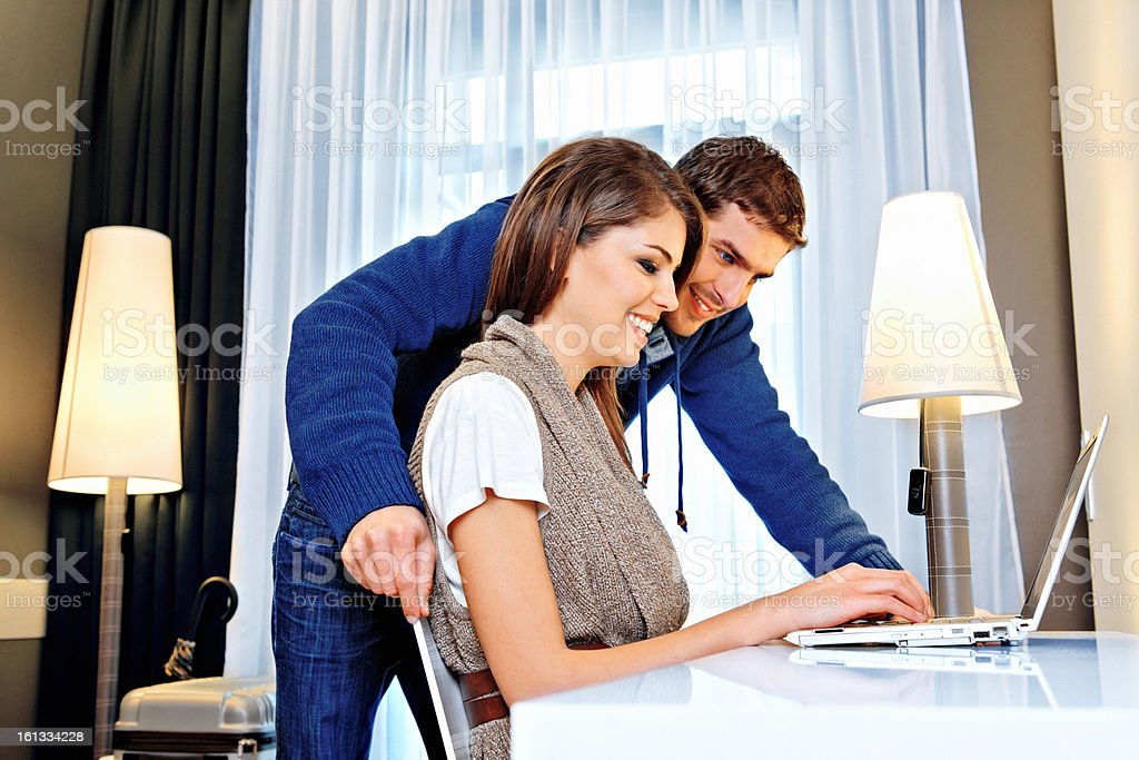 Young couple using computer in a hotel room royalty-free stock photo