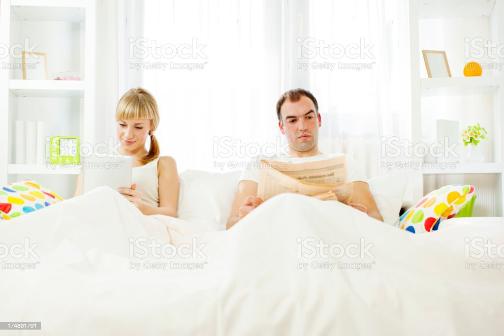 Young Couple Using Digital Tablet in Bed. royalty-free stock photo