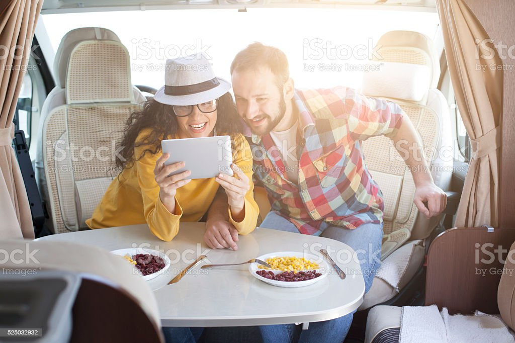 Young couple using digital tablet inside of caravan stock photo