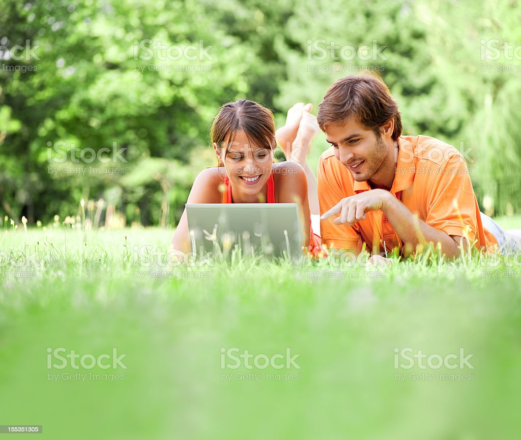 Young couple using laptop, outdoors royalty-free stock photo