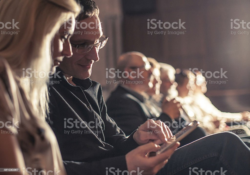 Young couple using smartphone between Theatre show royalty-free stock photo