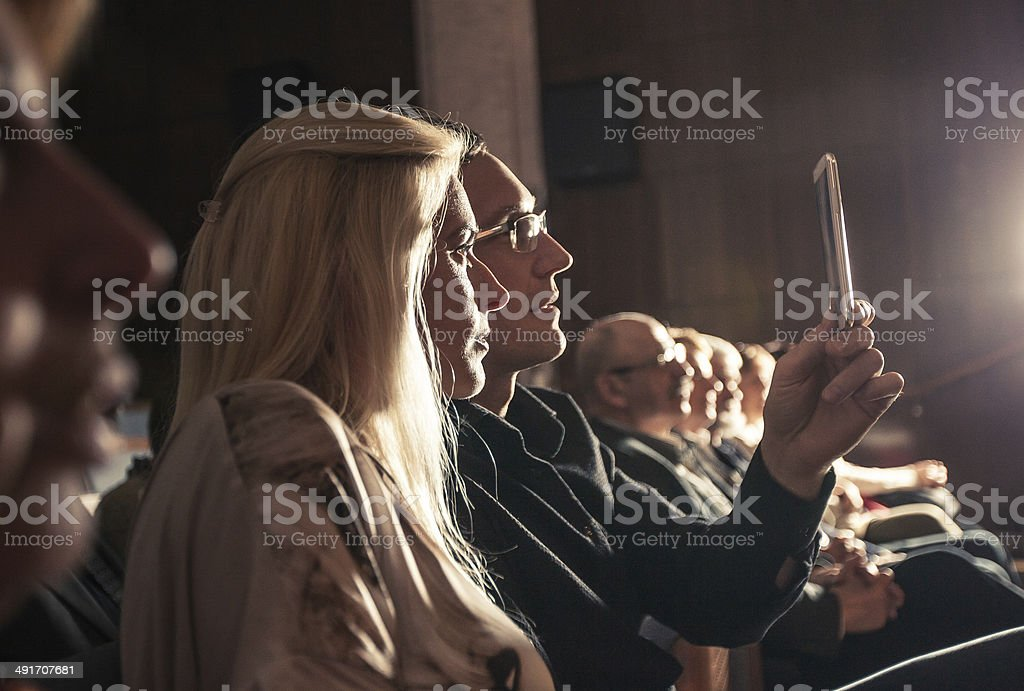Young couple using smartphone between Theatre show stock photo