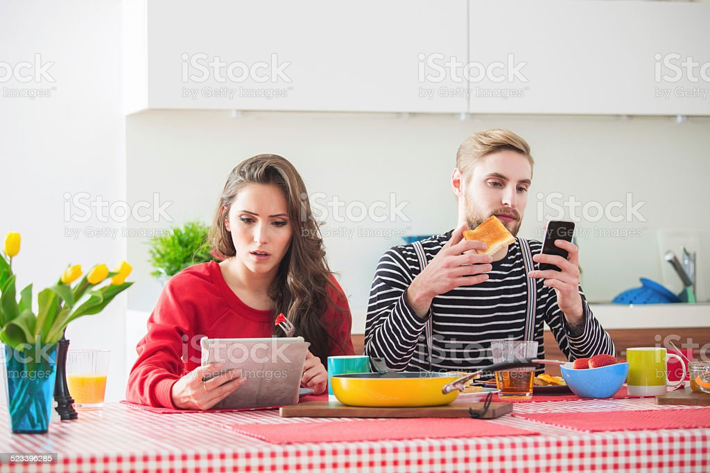 Young couple using technologies during breakfast stock photo