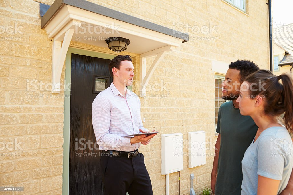 Young couple viewing a house with male real estate agent stock photo