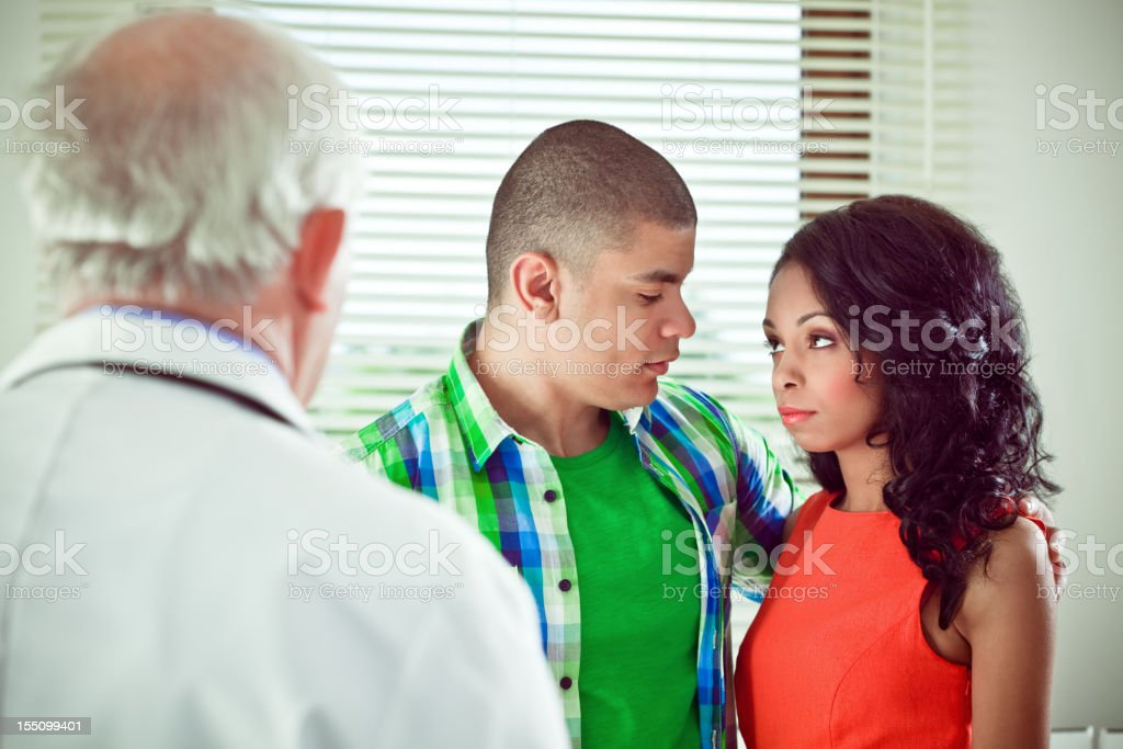 Young couple visiting a senior doctor royalty-free stock photo