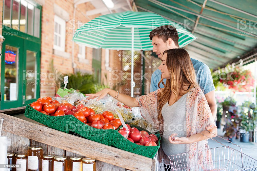 Young couple waiting a baby making grocery at farmer market stock photo
