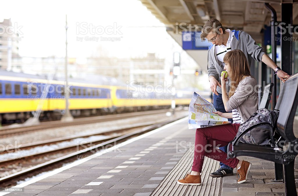 young couple waiting for the train, looking at map stock photo