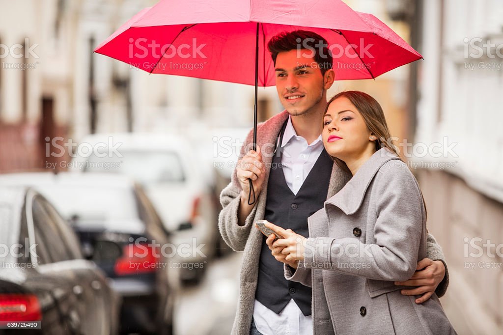 Young couple waiting on the street with mobile device stock photo