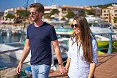 young couple walking along mediterranean promenade