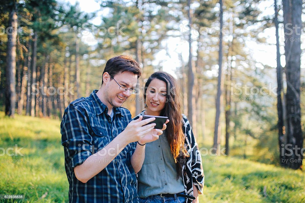 Young couple walking and using smartphone in the woods stock photo