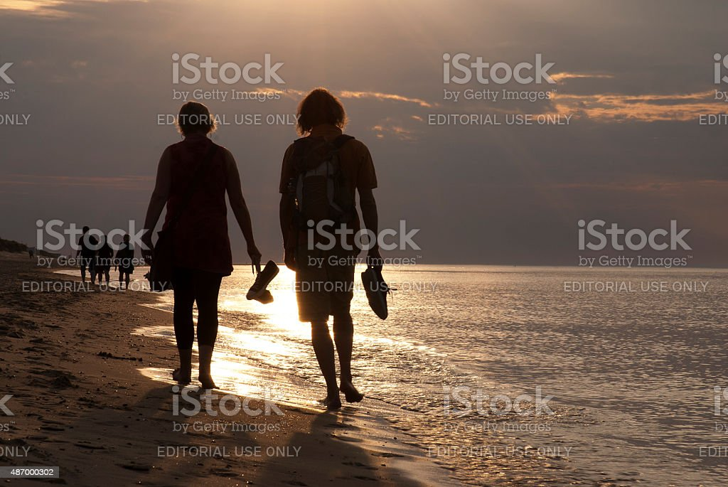 Young couple walking barefoot along sea beach at dusk stock photo
