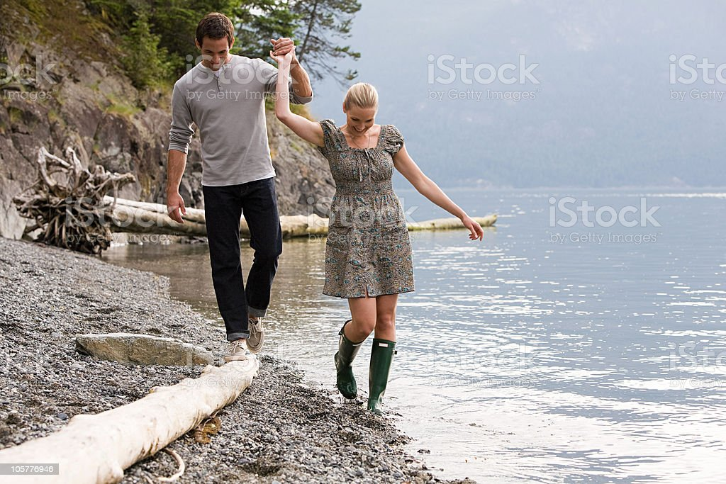 Young couple walking by lake holding hands royalty-free stock photo