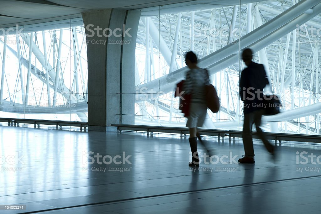 Young Couple Walking Down Corridor in Airport, Blurred Motion royalty-free stock photo