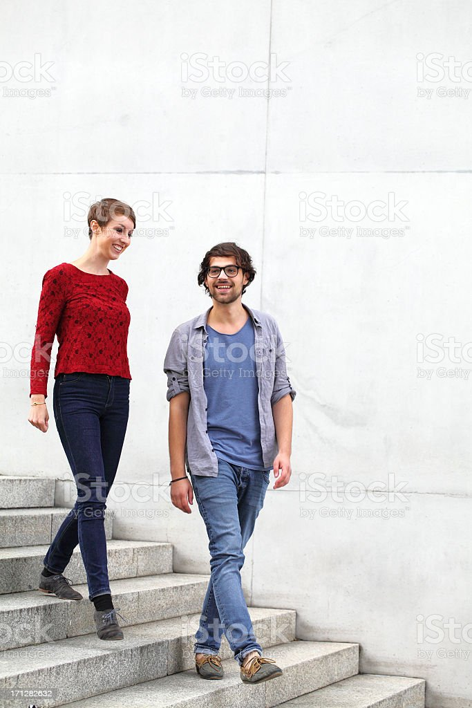 young couple walking down some concrete steps stock photo