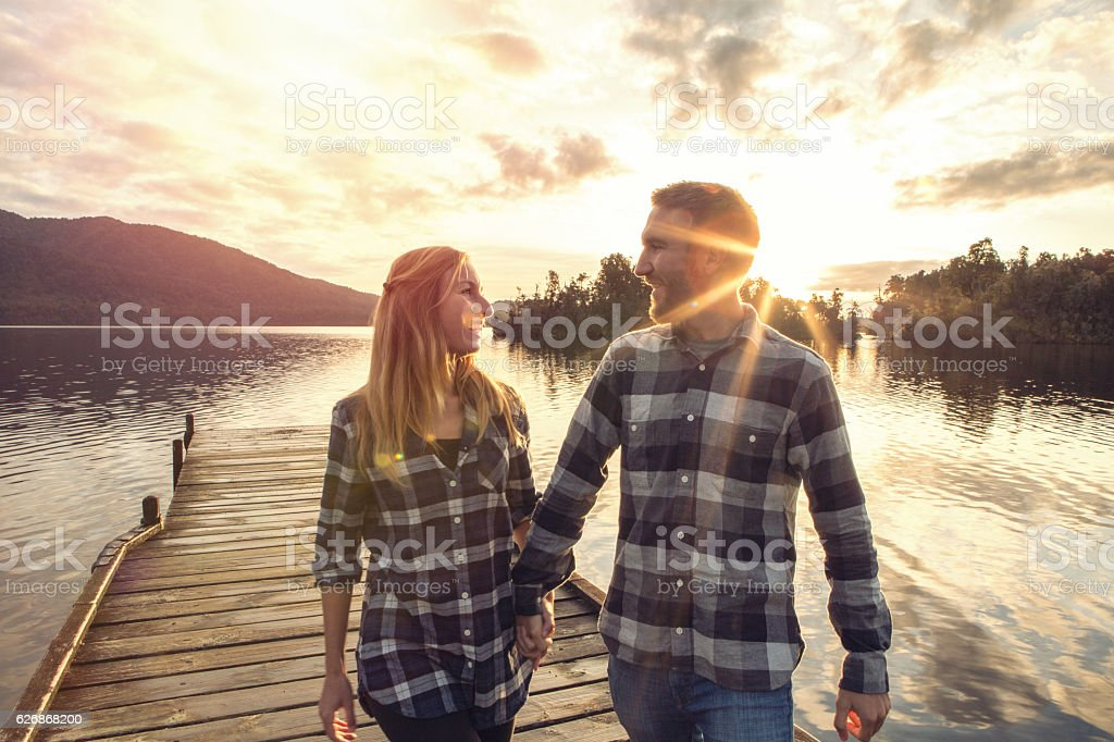 Young couple walking hand to hand on wooden pier stock photo