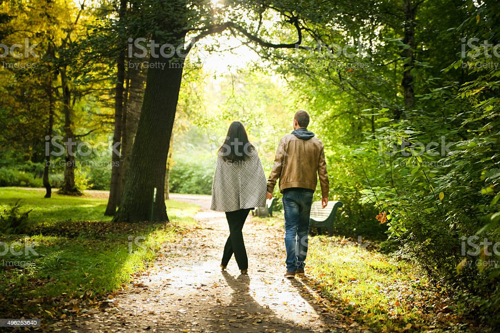 Young couple walking in a fall park stock photo
