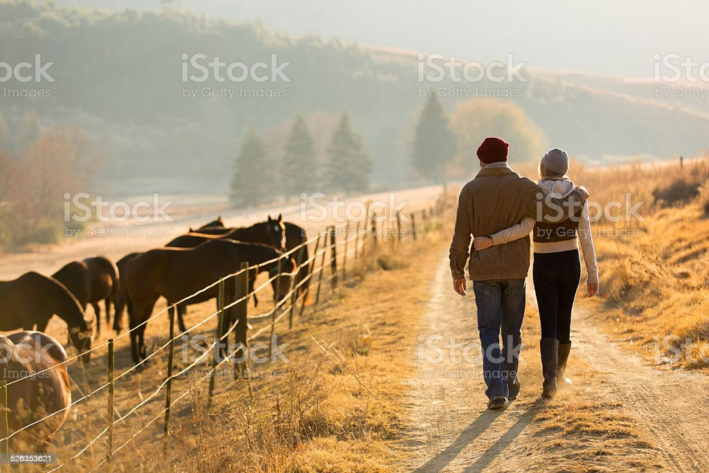 young couple walking in farm road stock photo