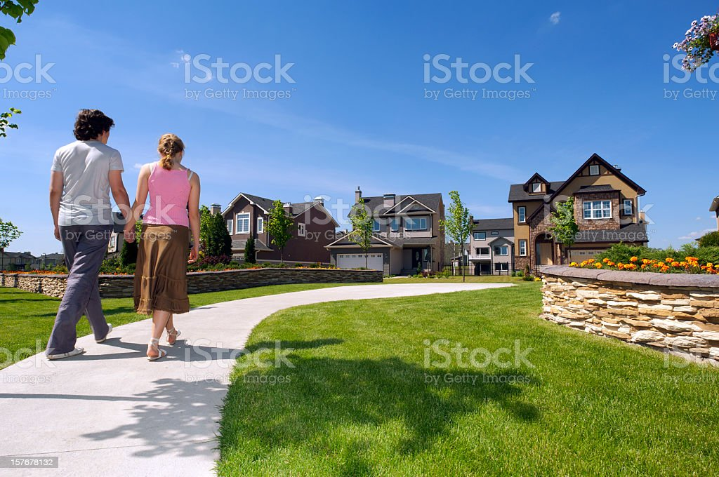Young couple walking in the suburbs towards a house stock photo