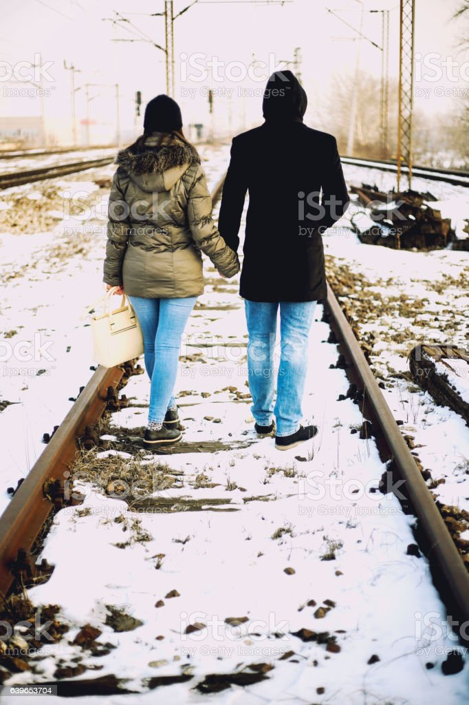Young couple walking on a railway stock photo