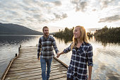 Young couple walking on wooden pier above lake