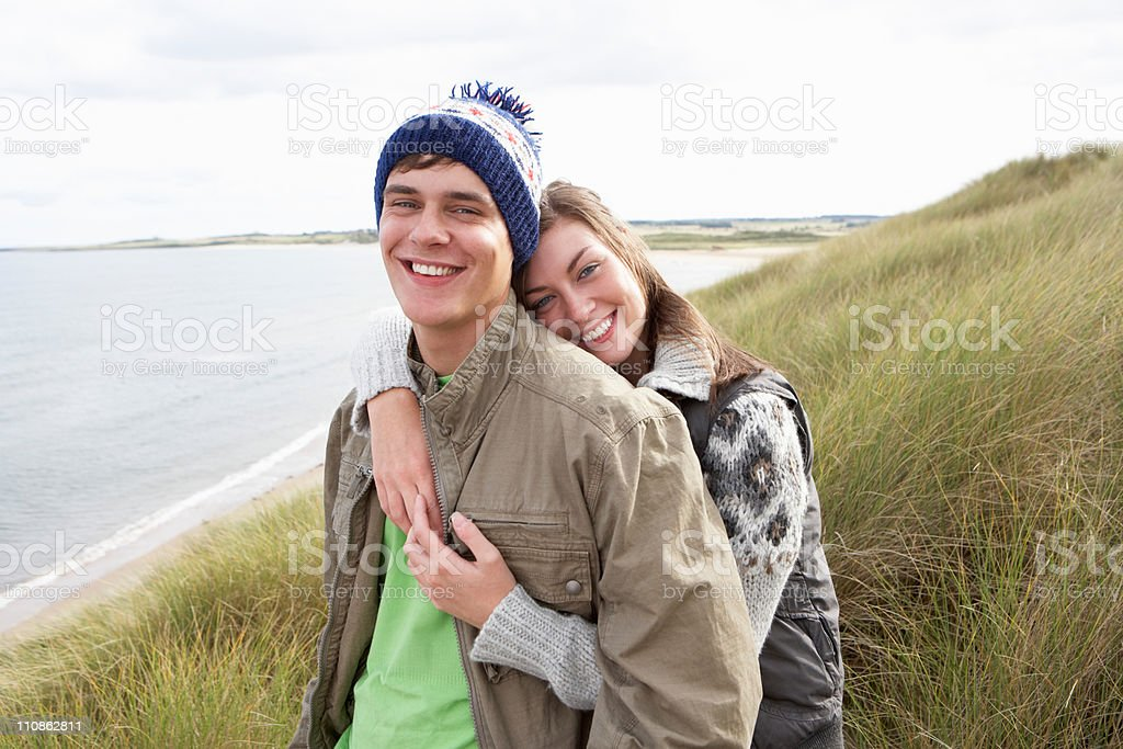 Young Couple Walking Through Sand Dunes Wearing Warm Clothing royalty-free stock photo