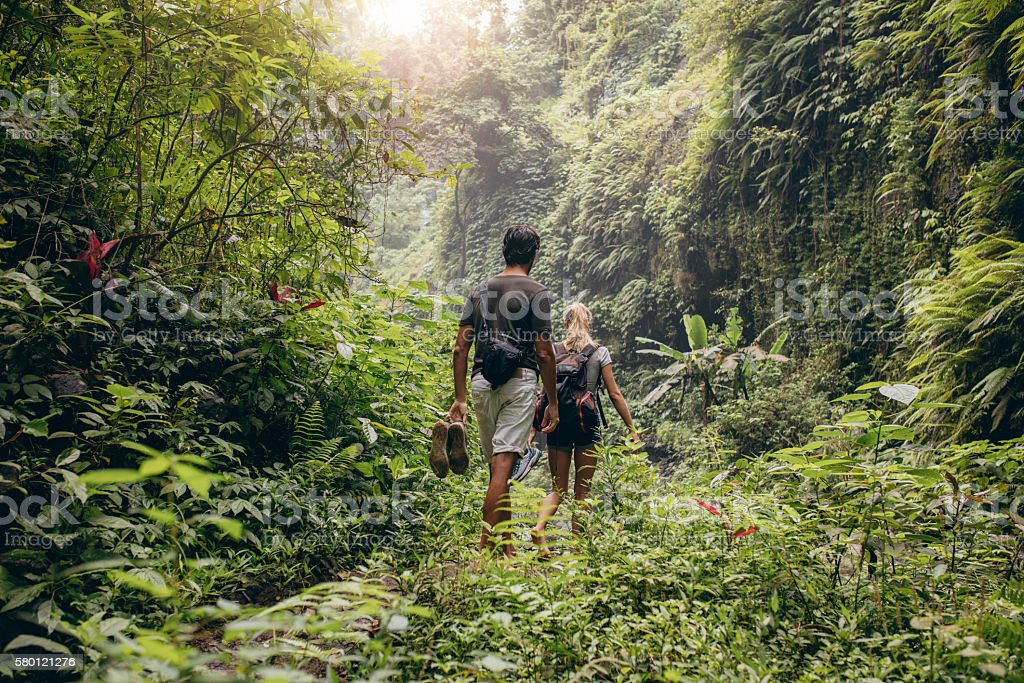 Young couple walking through woods stock photo