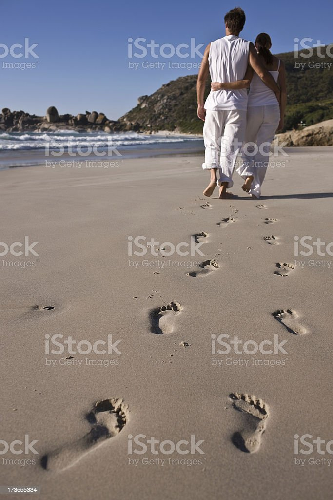 Young couple walking together on beach royalty-free stock photo