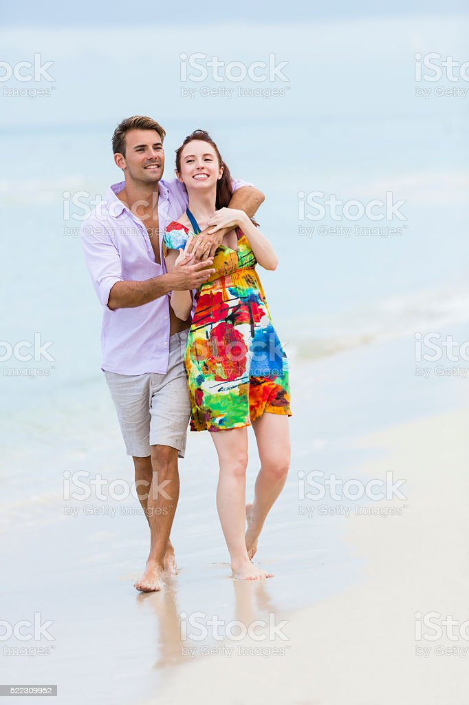 Young couple walking while hugging on the beach stock photo