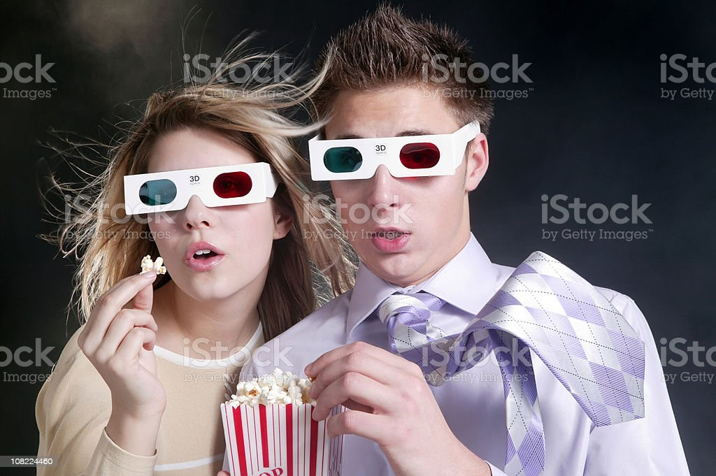 young couple watching 3d movie with popcorn royalty-free stock photo