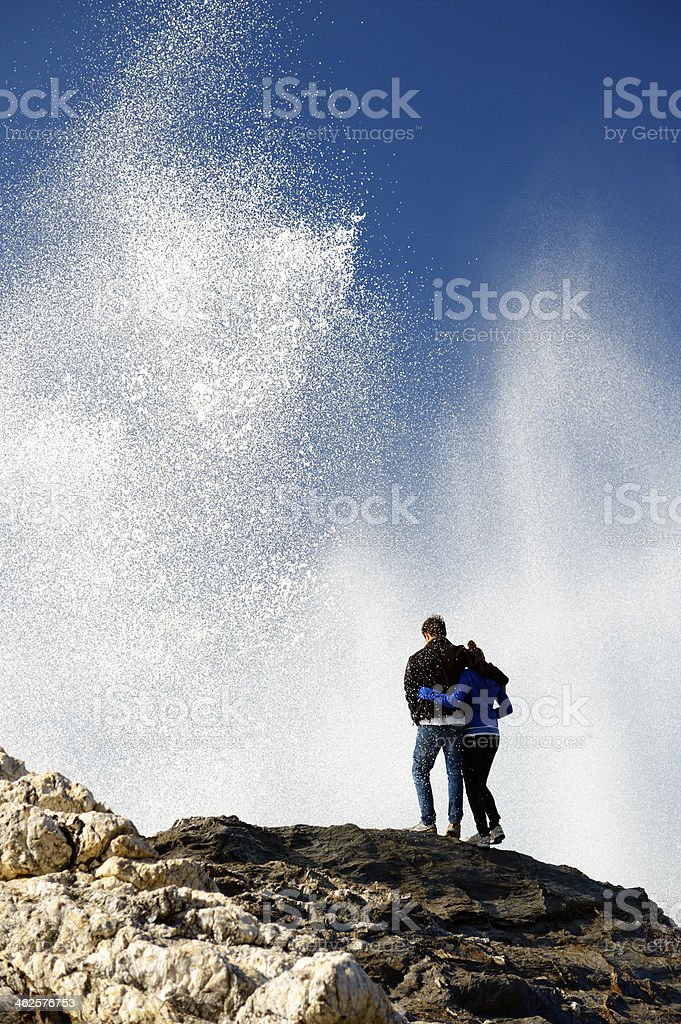 Young couple watching a huge wave splash stock photo