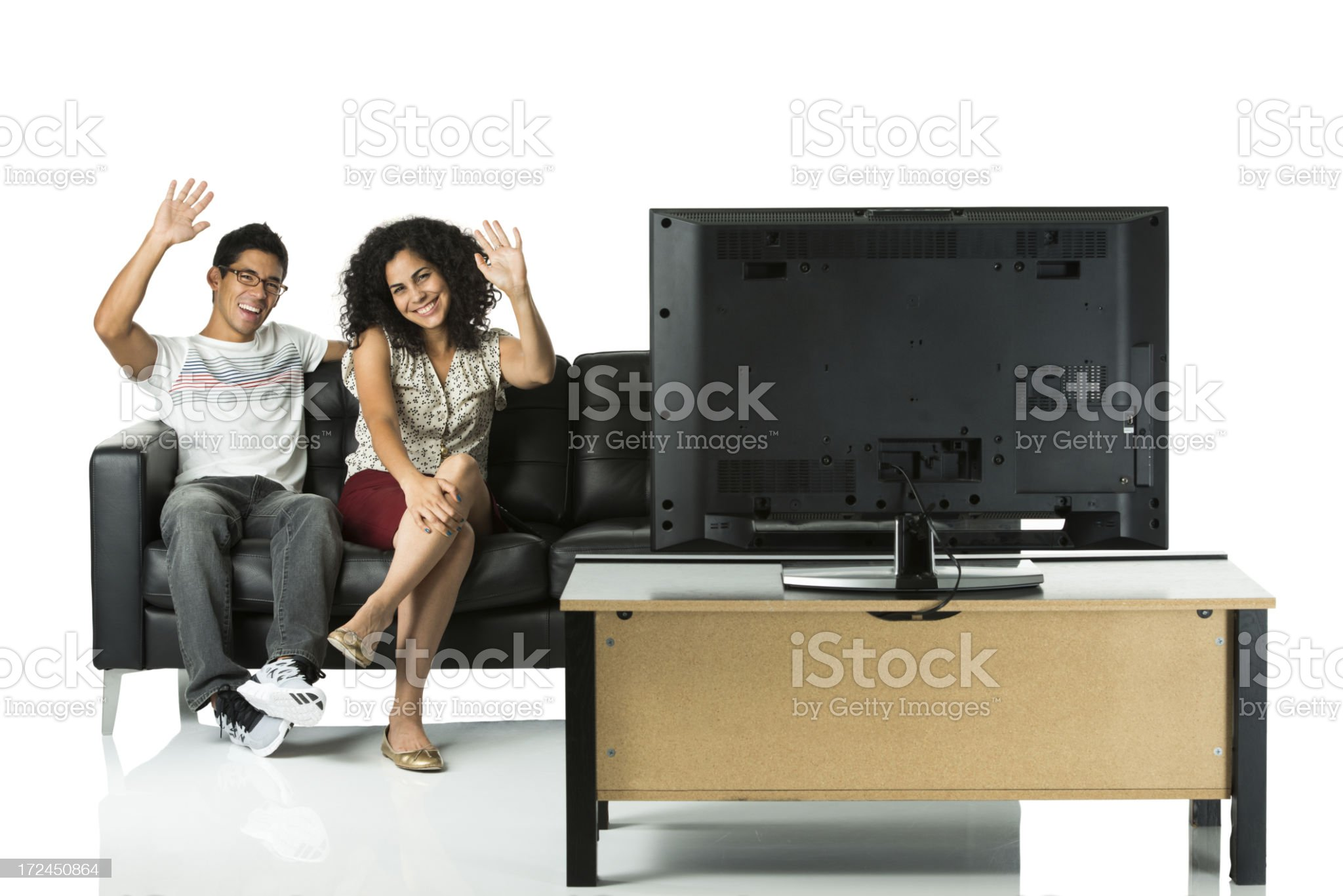 Young couple watching television and waving hands royalty-free stock photo