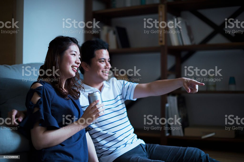 Young couple watching television at home. stock photo