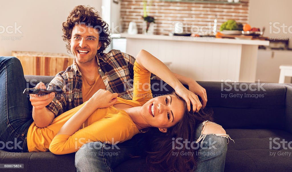 Young couple watching television together stock photo