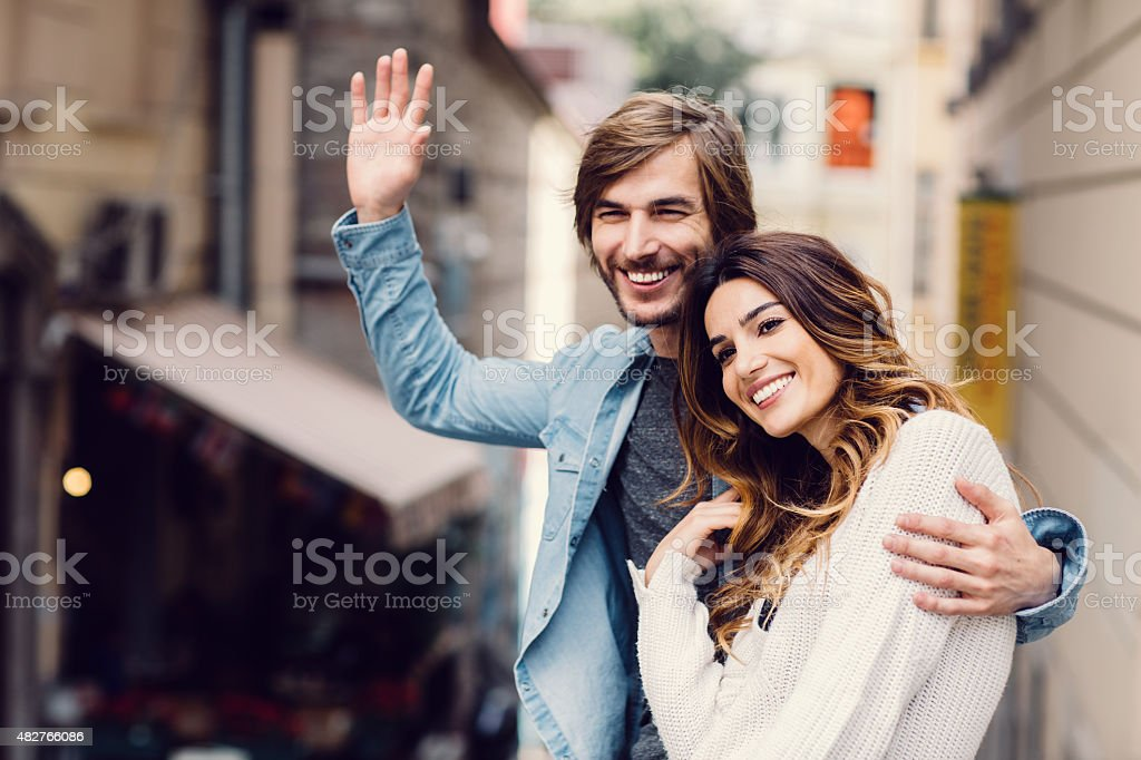 Young couple waving to a friend stock photo