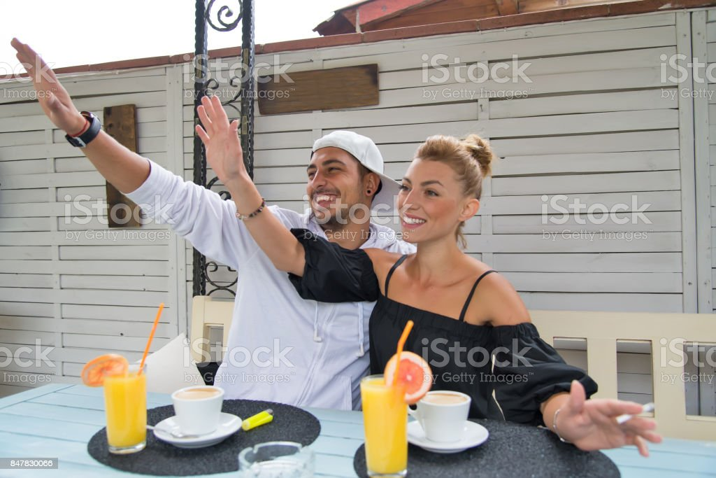 Young couple waving to friends. Human relationships.