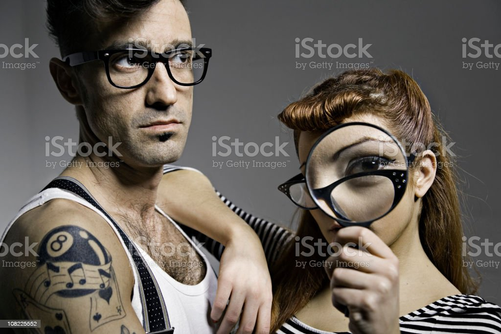 Young Couple Wearing Glasses and Holding Magnifying Glass royalty-free stock photo