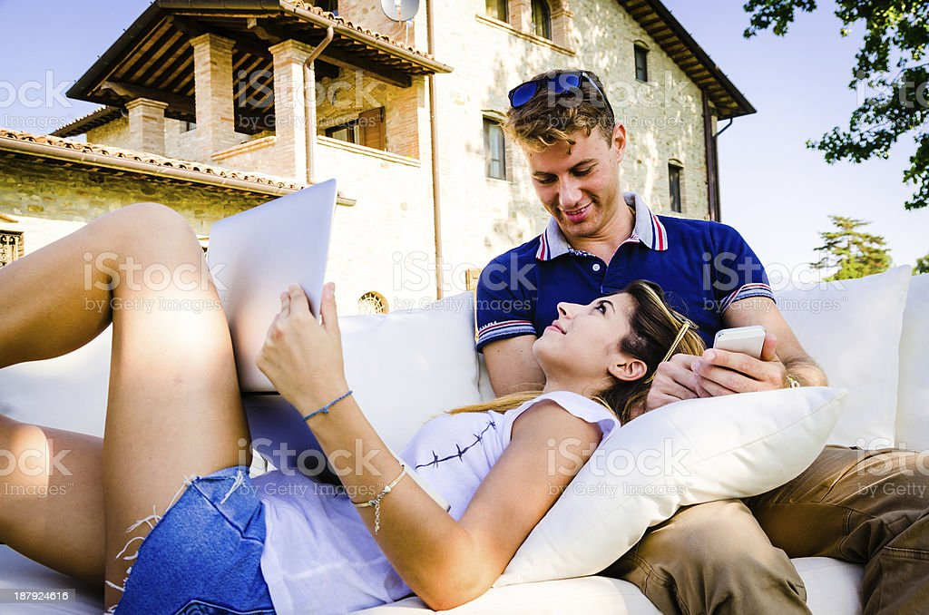 Young couple while using mobile phone and notebook royalty-free stock photo