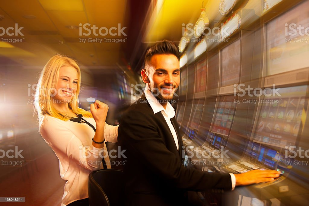 young couple winning on slot machine in casino stock photo