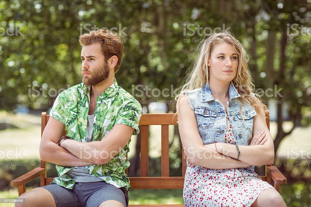 Young couple with arms crossed sitting on a park bench stock photo