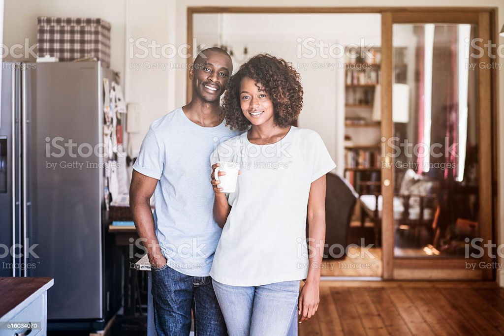 Young couple with coffee cup standing at home stock photo