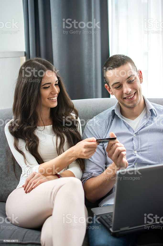 Young couple with credit card and laptop. stock photo