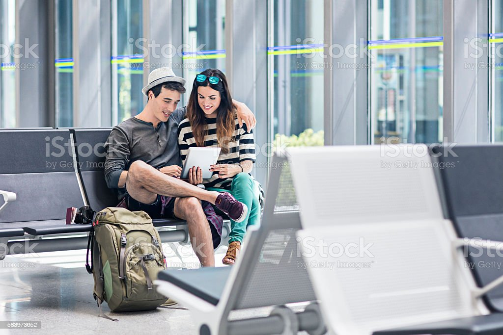 Young couple with digital tablet at airport stock photo
