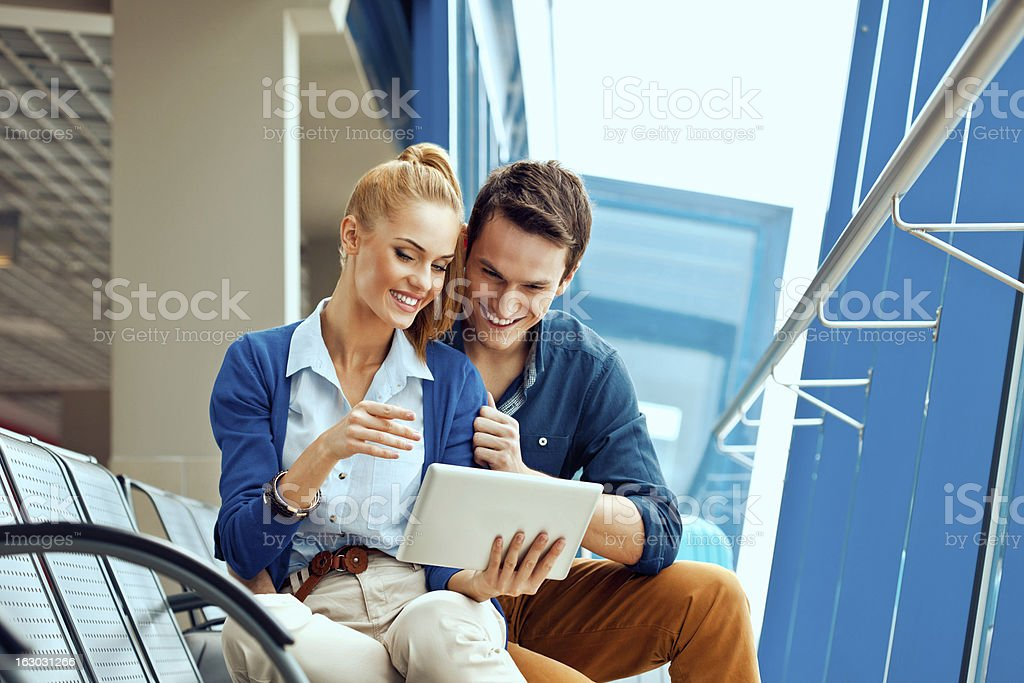 Young couple with digital tablet at the airport royalty-free stock photo
