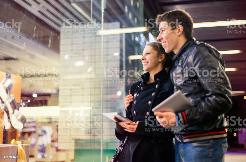 Young couple with digital tablets looking at store window stock photo