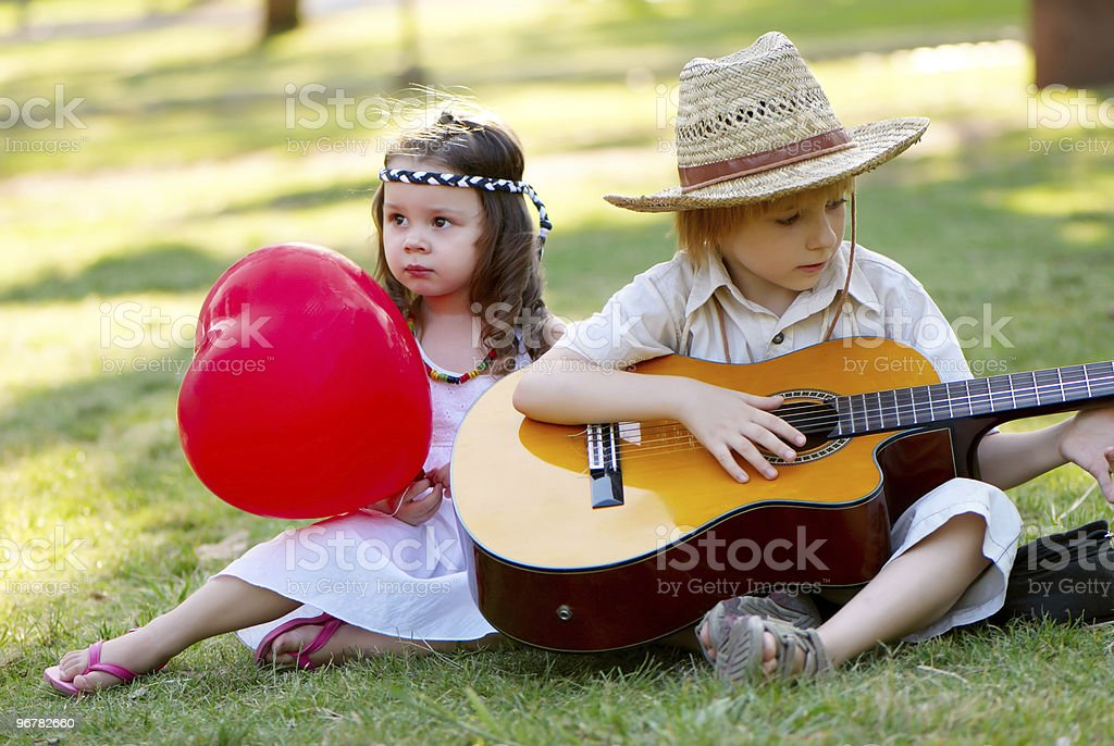 Young couple with guitar on grass in park royalty-free stock photo