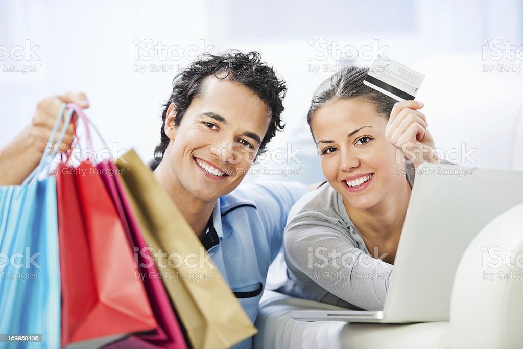 Young couple with laptop, shopping bags and credit card royalty-free stock photo