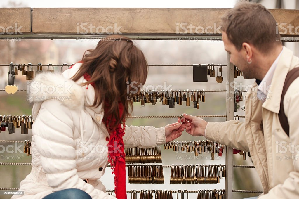 young couple with love padlocks on the bridge stock photo