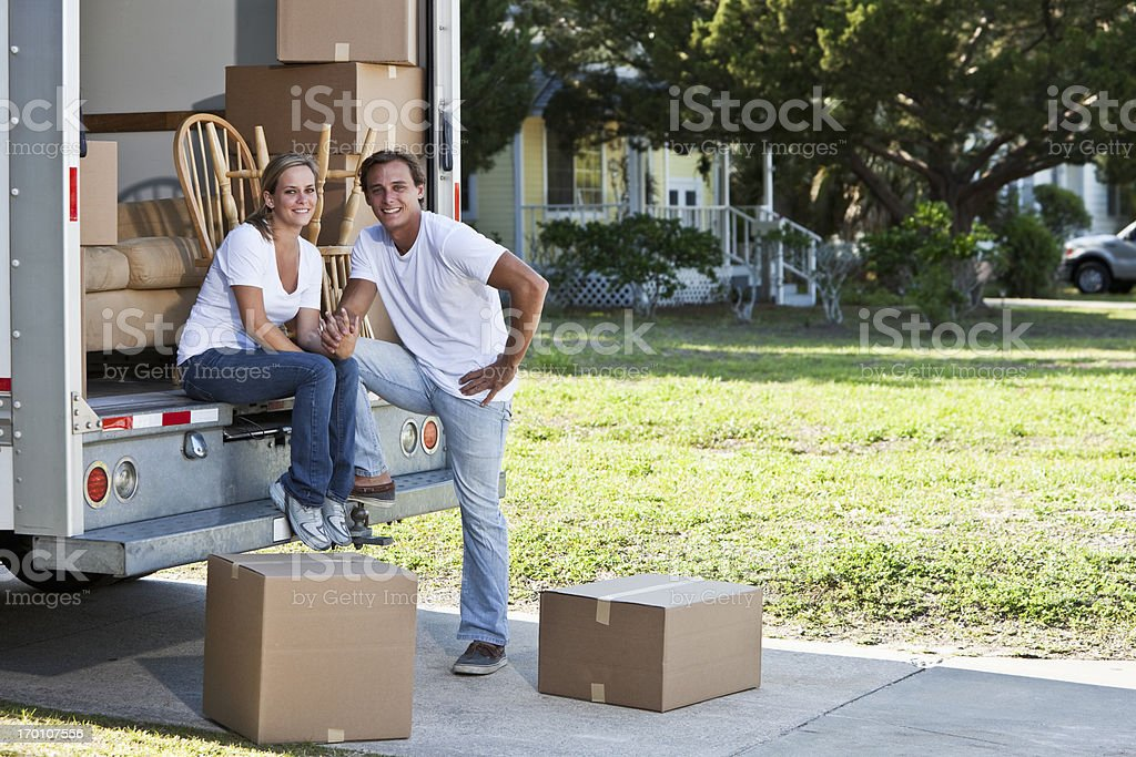 Young couple with moving truck stock photo